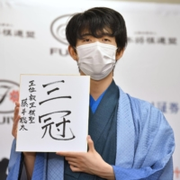 Shogi start Sota Fujii holds up a sign that reads 'three titles' after having won the Eio title in Tokyo on Monday.   KYODO