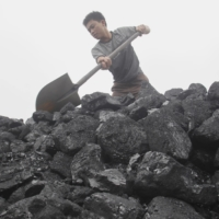 A worker shovels coal as he loads a truck at a coal port in Hanoi. | REUTERS