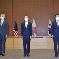 Sung Kim (from left to right), Takehiro Funakoshi and Noh Kyu-duk, senior envoys on North Korean policies from the U.S., Japan, and South Korea, pose ahead of their meeting in Tokyo on Tuesday. | POOL / VIA REUTERS