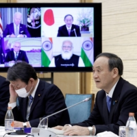 Prime Minister Yoshihide Suga speaks while a monitor displays U.S. President Joe Biden, Australian Prime Minister Scott Morrison and Indian leader Narendra Modi during a virtual 'Quad' meeting at Suga's official residence in Tokyo in March.   POOL / VIA REUTERS