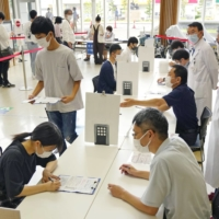 High school students gather to get COVID-19 vaccines in Aichi Prefecture on Sunday.   KYODO