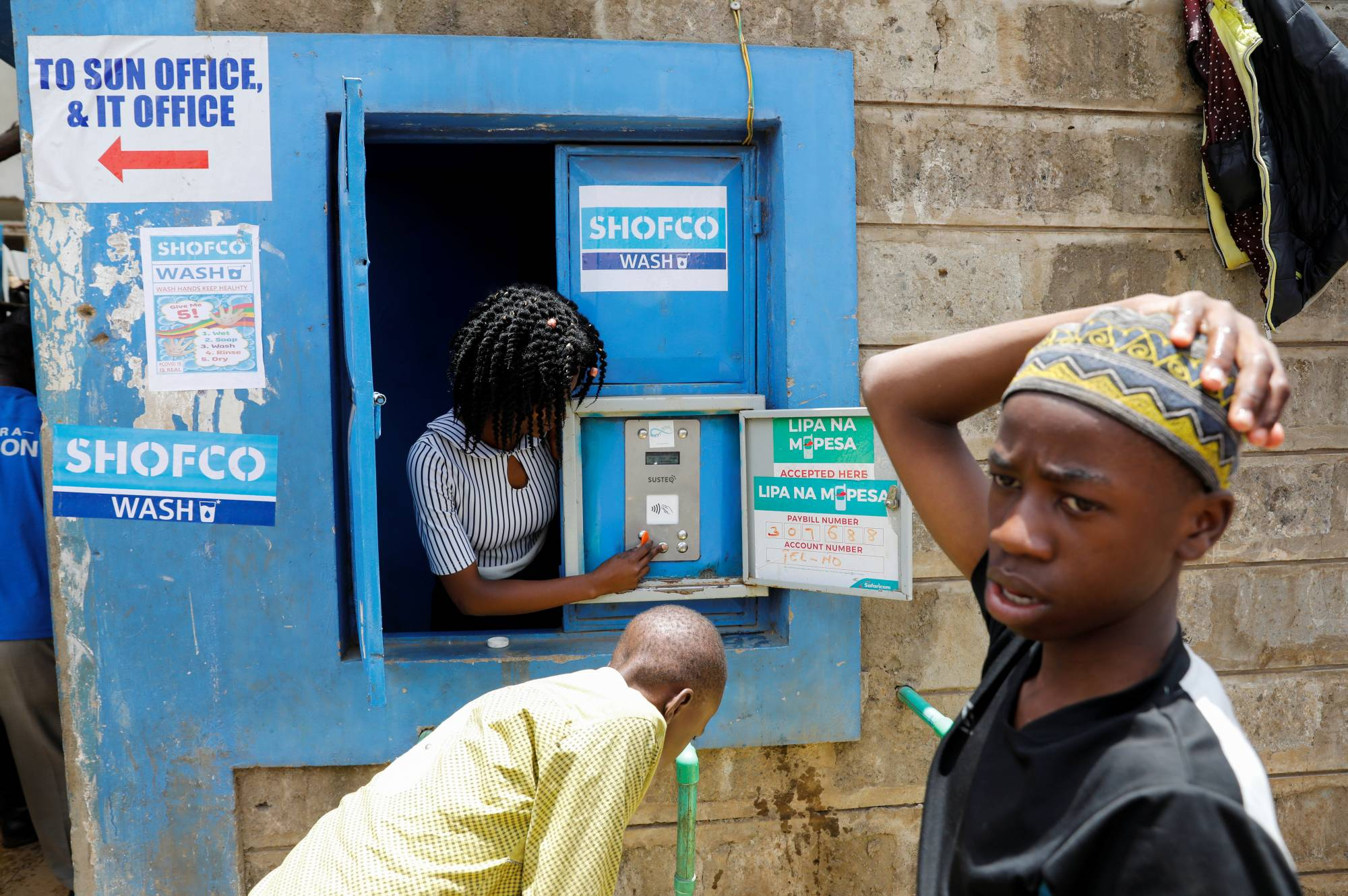 An employee of community organization Shining Hope for Communities (SHOFCO) activates a water selling machine in the Kibera slum in Nairobi. | REUTERS