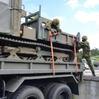 Ground Self-Defense Force members load a vehicle onto a truck Wednesday, the first day of nationwide military exercises. | GROUND SELF-DEFENSE FORCE / VIA KYODO