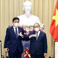 Vietnam's President Nguyen Xuan Phuc (R) bumping elbows to greet Japan's Defence Minister Nobuo Kishi during a meeting in Hanoi on Sunday. | VIETNAM NEWS AGENCY / AFP-JIJI