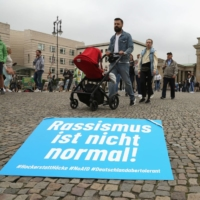 A sign reading 'Racism is not normal,' referring to the Alternative for Germany party slogan 'Germany, but normal' during a demonstration on Sept. 4 in Berlin | AFP-JIJI