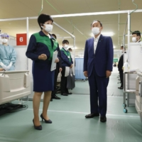 Prime Minister Yoshihide Suga and Tokyo Gov. Yuriko Koike visit a so-called oxygen station at the former site of Tsukiji fish market in Tokyo on Thursday before its official opening. | KYODO