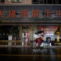 A woman drives a motorbike past the facade of an Evergrande housing complex in Shenzhen on Thursday. | AFP-JIJI