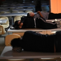 Evergrande investors and suppliers sleep on dining tables at a canteen near the Evergrande headquarters in Shenzhen on Thursday. | AFP-JIJI