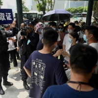 Police officers watch people gathering at the Evergrande headquarters in Shenzhen on Thursday. The Chinese property giant has said it is facing 'unprecedented difficulties' but denied rumors that it is about to go under. | AFP-JIJI