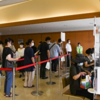 Residents wait in line to receive the COVID-19 vaccine at a mass vaccination site in Saitama on Aug. 23.   BLOOMBERG