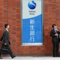 A man walks past a Shinsei Bank signboard at its branch in Tokyo. | REUTERS