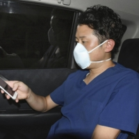 A doctor reports to a public health center with his smartphone in Osaka on Aug. 11. | KYODO