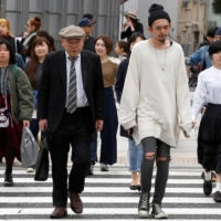 Pedestrians cross the street at a crosswalk in Tokyo's Omotesando shopping district. An analysis of ancient DNA is transforming the understanding of the genetic ancestry of Japan's modern-day population, identifying a crucial contribution from people who arrived about 1,700 years ago and helped revolutionize Japanese culture.