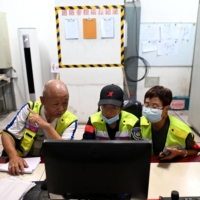 Volunteers review closed-circuit television footage in search of Chen Shaohua, who suffers from Alzheimer's, at a mall in Beijing where Chen disappeared in July. | AFP-JIJI