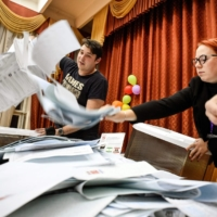 Members of a local electoral commission empty a ballot box at a polling station in Moscow on Sunday.    AFP-JIJI
