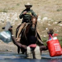 A U.S. border patrol officer cuts the way of a migrant asylum-seeker as he is trying to return to the United States along the Rio Grande river, after having crossed into Mexico to buy food, as seen from Ciudad Acuna, Mexico, on Sunday.  | REUTERS