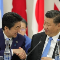 Then-Prime Minister Shinzo Abe greets Chinese leader Xi Jinping during the Group of 20 summit in Osaka in June 2019.   SPUTNIK / KREMLIN / VIA REUTERS