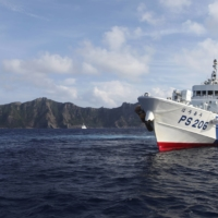A Japan Coast Guard vessel sails in front of Uotsuri Island, one of the Japanese-controlled Senkaku Islands, in the East China Sea in August 2013.   REUTERS
