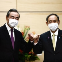 Prime Minister Yoshihide Suga bumps elbows with Chinese Foreign Minister Wang Yi at the start of their meeting in Tokyo last November.   POOL / VIA REUTERS