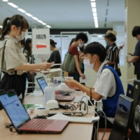 A visitor submits her documents at the reception of a COVID-19 vaccination center at Aoyama University in Tokyo on Aug. 2.   POOL / VIA REUTERS