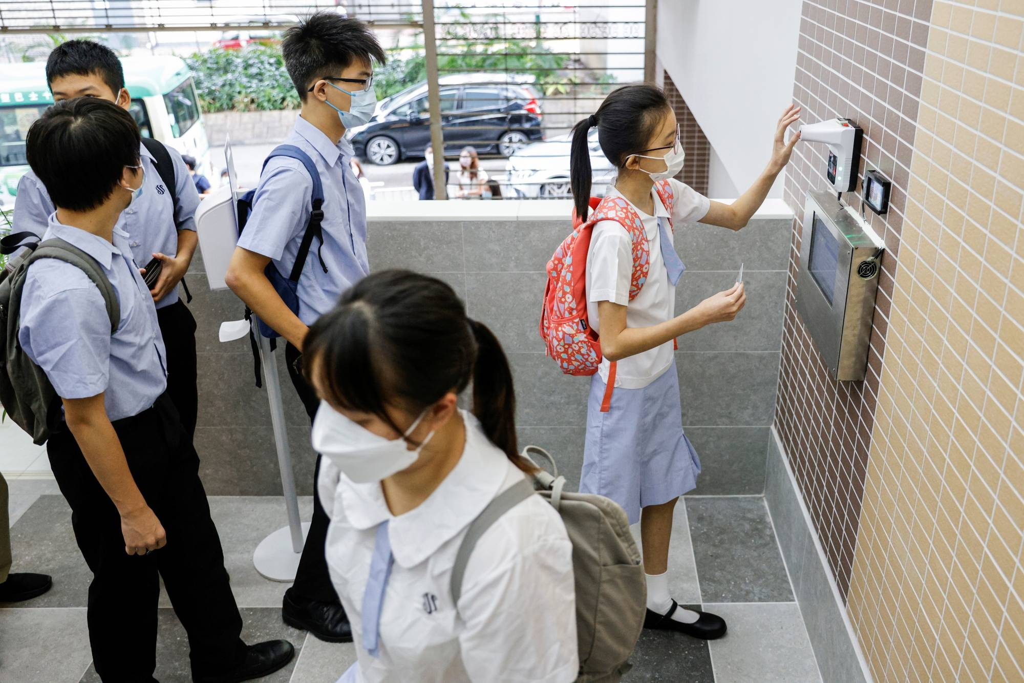 Students have their temperatures checked in Hong Kong. | REUTERS