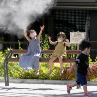 Children play under a misting machine in Tokyo's Ginza district as temperatures rose on Sunday.  |  KYODO