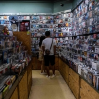 Customers look at movies for sale at a store inside a cinema in Hong Kong on Sept. 2.  | AFP-JIJI