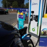 An electric taxi is charged at a BP Pulse charging point in London. | REUTERS