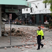 A person walks past damage to the exterior of a restaurant following an earthquake in the Windsor suburb of Melbourne on Wednesday.  |  AAP / VIA REUTERS