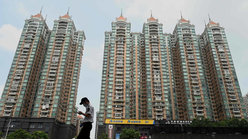 A man walks past a housing complex by embattled Chinese property developer Evergrande in Guangzhou on Friday.