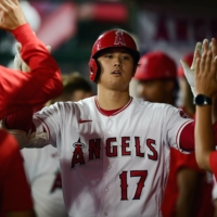 Angels designated hitter Shohei Ohtani celebrates with his teammates after hitting a solo home run against the Astros on Tuesday in Anaheim, California. | USA TODAY / VIA REUTERS