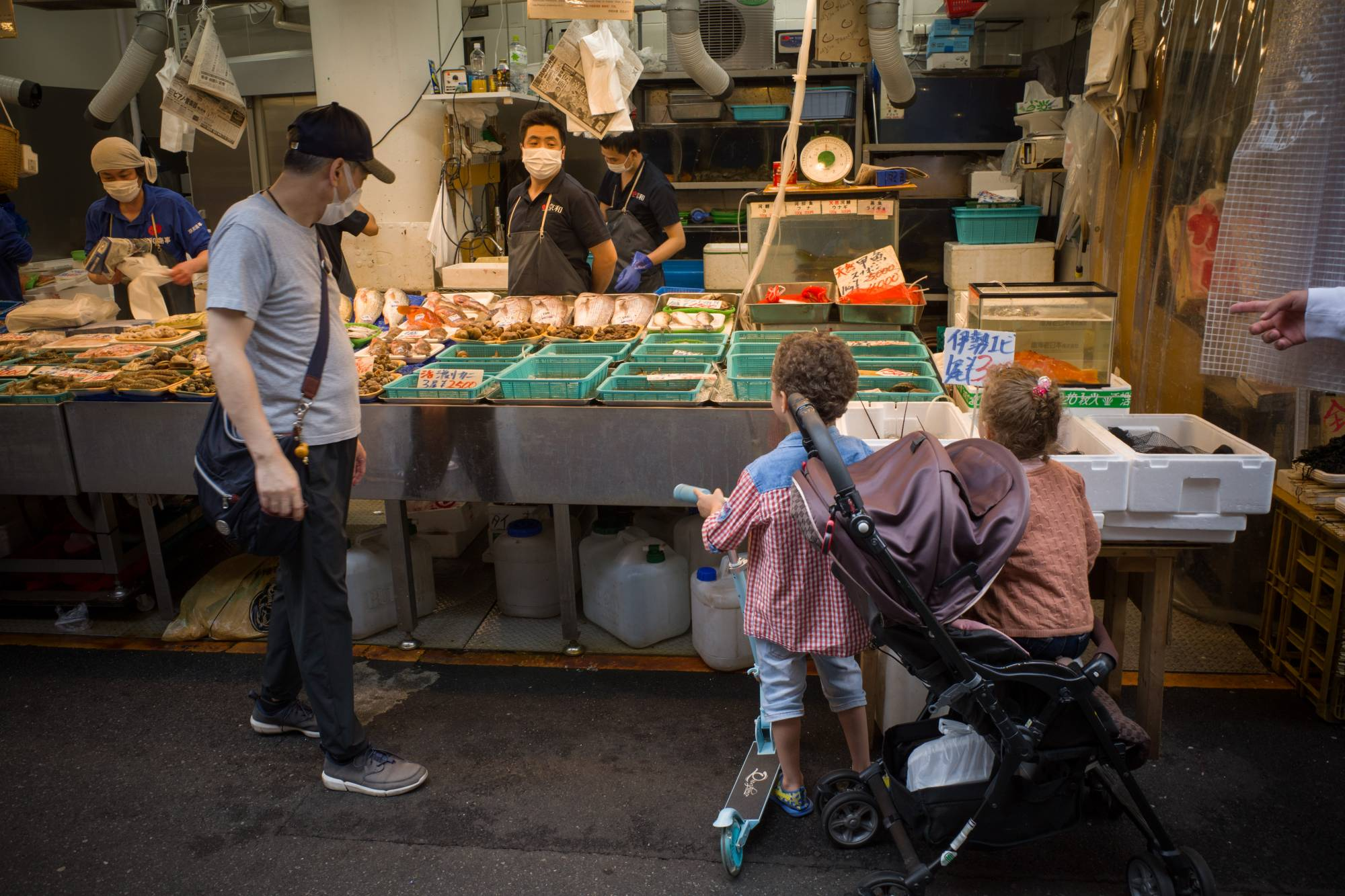 Children stop in front of a seafood stall at the Ameyoko market in Tokyo earlier this month.  | BLOOMBERG