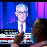 A screen displays a statement by U.S. Federal Reserve Chair Jerome Powell as a trader works on the floor of the New York Stock Exchange on Wednesday. | REUTERS