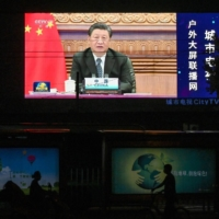 A large screen shows a news program featuring Chinese leader Xi Jinping speaking via video at the opening of the virtual BRICS Summit, on a street in Beijing, on Sept. 10. | AFP-JIJI