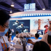 A staff member attends to visitors who learn about the cotton plants on display at the Xinjiang booth at the 2021 China International Trade in Services Fair in Beijing on September 4.  |  REUTERS