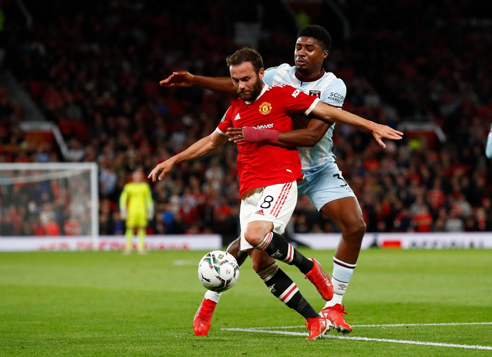 Manchester United's Juan Mata (front) and West Ham's Ben Johnson vie for the ball during their League Cup match in Manchester, England, on Wednesday | REUTERS