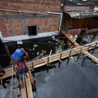 A man carries drinking water on a platform over a flooded street in Manaus, Amazonas state, Brazil, in May. | REUTERS