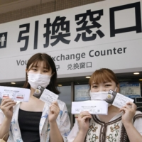 Visitors at a baseball game held at PayPay Dome in Fukuoka show their vaccination certificates along with tickets. | KYODO