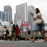 A street in front of high-rise buildings in the Shinjuku district of Tokyo.