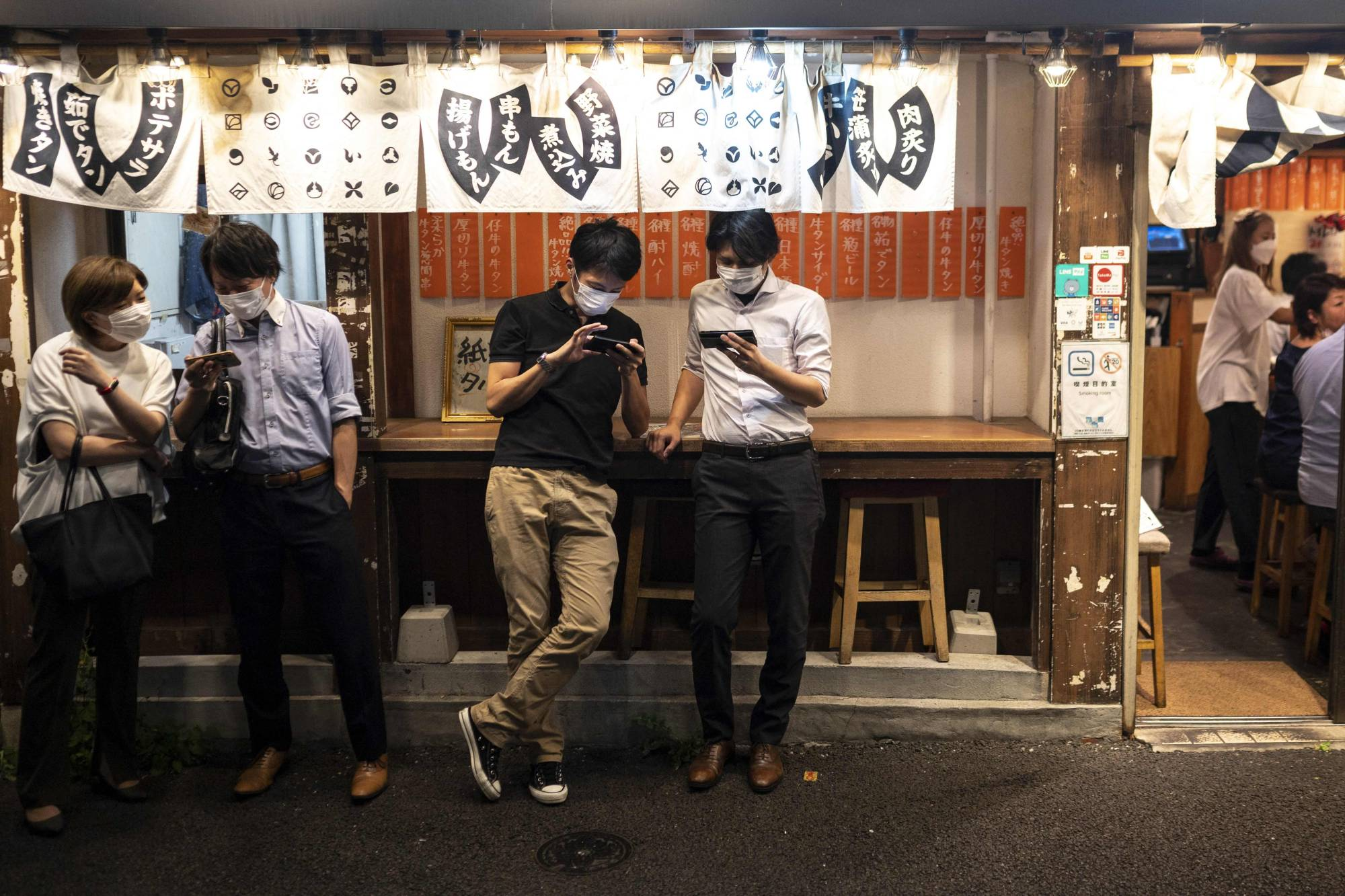 Evening diners wait for vacant seats at a restaurant in Tokyo on Friday. | AFP-JIJI