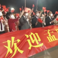 People wave Chinese flags behind a banner welcoming Huawei Technologies Chief Financial Officer Meng Wanzhou as she arrives in Shenzhen on Saturday.    CCTV / VIA REUTERS
