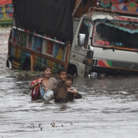 Children wade along a flooded street after a heavy downpour in Lahore, Pakistan, on Sept. 11. | AFP-JIJI