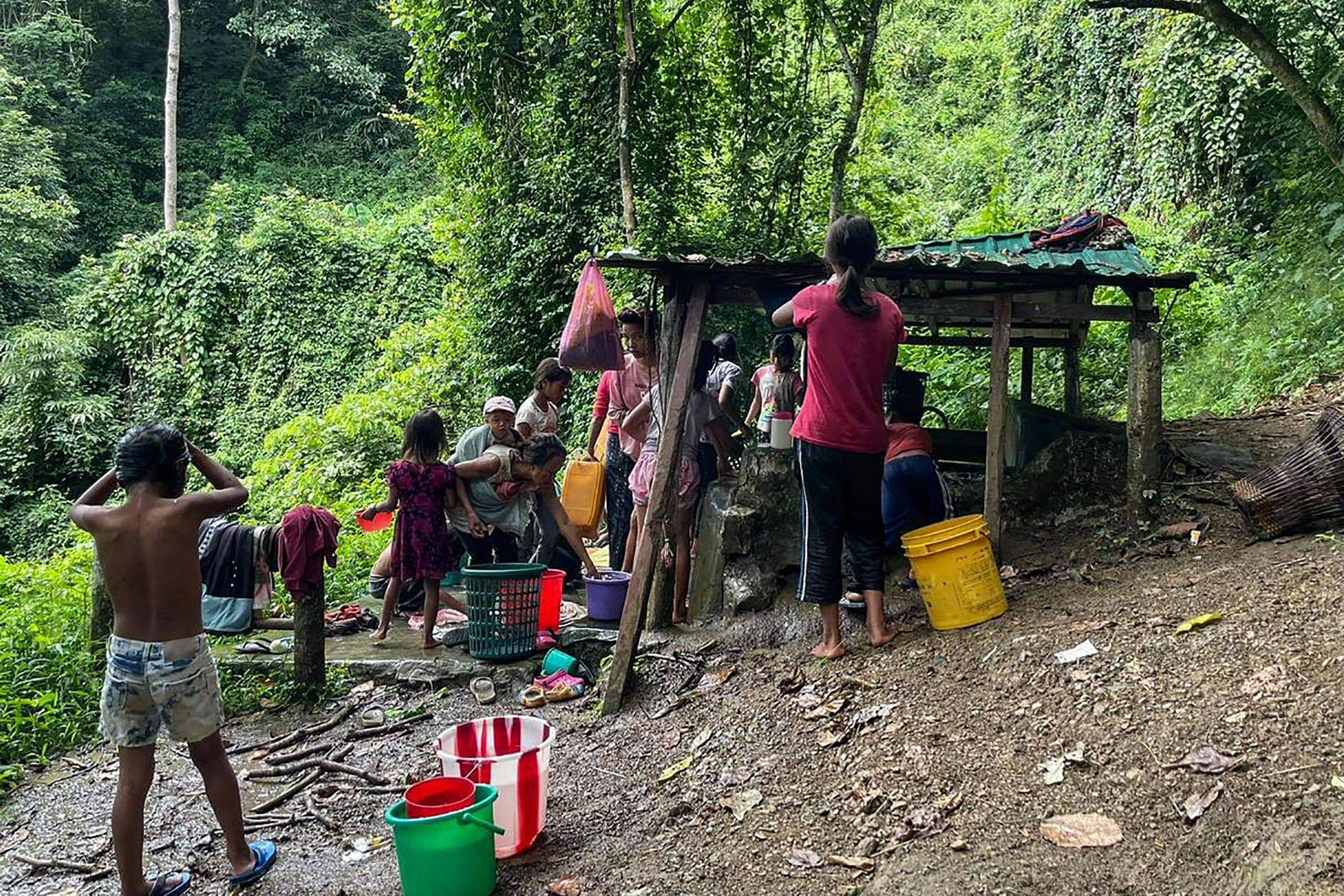 Refugees collect water at Pang village in India's eastern state of Mizoram, near the Myanmar border on Friday, after people fled following attacks by Myanmar's military on villages in western Chin state. | AFP-JIJI