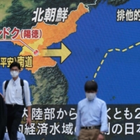 Pedestrians walk past a screen displaying a map detailing a North Korean missile launch, during a news broadcast in Tokyo's Akihabara area on Sept. 16. | AFP-JIJI