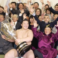 Then-ozeki Hakuho celebrates his first top-division title with supporters, including father Jigjidiin Monkhbat (front right), after the 2006 May Basho at Ryogoku Kokugikan. | KYODO