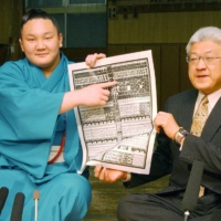 Hakuho, sitting next to Miyagino stablemaster, points to his name on the banzuke rankings after his promotion to the makuuchi division in April 2004. | KYODO