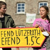 Climate activists Luisa Neubauer and Greta Thunberg hold a sign while giving a press statement in Luetzerath, Germany, on Saturday.   AFP-JIJI