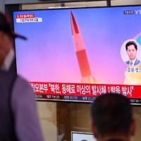 People watch a TV news broadcast showing file footage of a North Korean missile test, at a railway station in Seoul on Tuesday. | AFP-JIJI