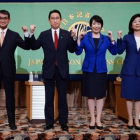 The four candidates in the ruling Liberal Democratic Party presidential election —  vaccination minister Taro Kono (from left), former Foreign Minister Fumio Kishida, onetime internal affairs ministers Sanae Takaichi and Seiko Noda — strike a pose ahead a debate at the Japan National Press Club in Tokyo on Sept. 18. | POOL / VIA AFP-JIJI