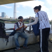 A Chilean missionary hands out goods to homeless people living by the Sumida River in Tokyo on Sept. 22.   ALEX K.T. MARTIN